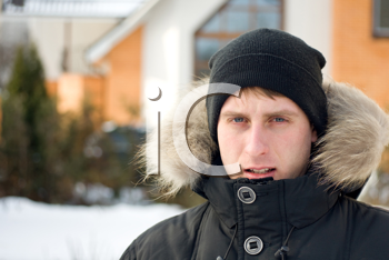 Winter time - man in cap and warm jacket with furry hood in the yard