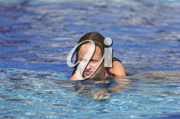 Girl is having fun in a pool at the tropical resort.