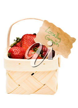Strawberries and a tag in a wicker basket isolated over white
