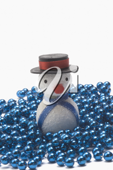 Close-up of a snowman on string of blue beads