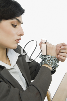 Businesswoman's hands tied up with a chain