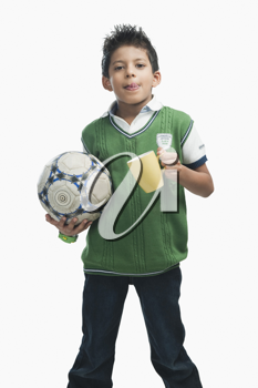 Boy holding a soccer ball and drinking hot chocolate