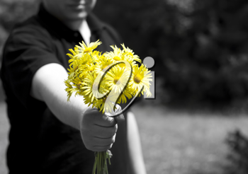 Man giving a present with yellow daisy flowers. Focus on flowers.