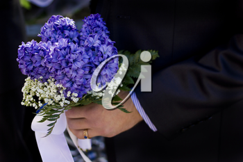 Man hold beautiful colorful wedding flowers in hand