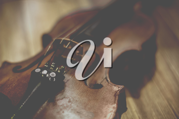 Vintage old violin lying on a wooden surface