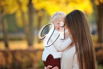 A young mother in a sweater holds her cute blonde daughter in her arms during a walk in the autumn Park, against the background of fallen leaves and trees