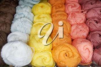 Threads for knitting different colors on the shelf in the store.