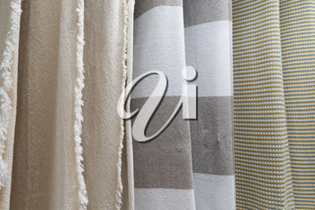 Different blankets of different colors, warm and cozy hang on the stand for sale. Rugs hang on the stand in the store.