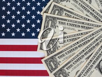 One Dollar banknotes (USD) currency money over the flag of the United States