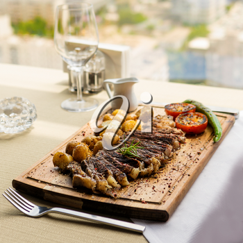 Tasty steak with potato, vegetable on the wood plate