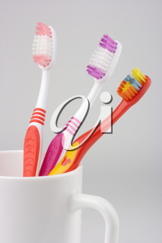 Royalty Free Photo of Three Toothbrushes in a Mug