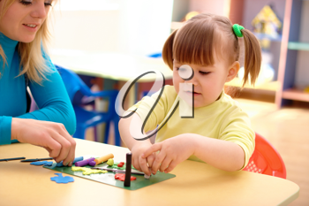 Royalty Free Photo of a Little Girl and Teacher Playing With Plasticine