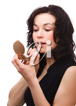 Royalty Free Photo of a Young Woman Applying Lipstick
