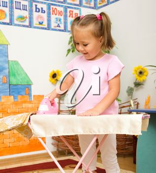 Royalty Free Photo of a Little Girl With a Toy Ironing Board