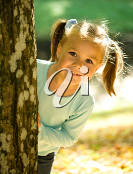 Royalty Free Photo of a Little Girl Playing Outside in Autumn