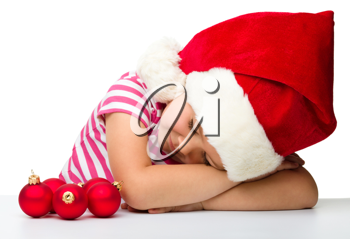 Royalty Free Photo of a Little Girl in a Santa Hat Sleeping Beside Ornaments