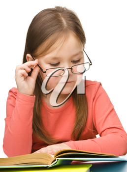 Cute little girl reading book wearing glasses, isolated over white