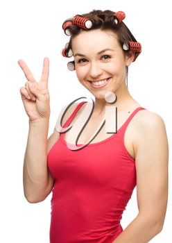 Young woman dressed in red is showing victory sign while wearing hair-rollers, isolated over white