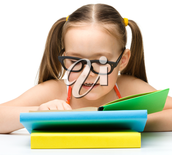 Cute little girl is reading book while wearing glasses, isolated over white