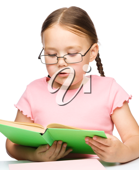 Cute little schoolgirl with a book wearing glasses, isolated over white