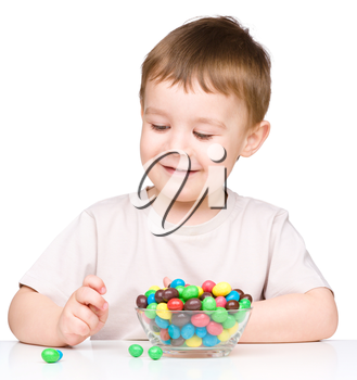 Portrait of a boy with colorful candies, isolated over white