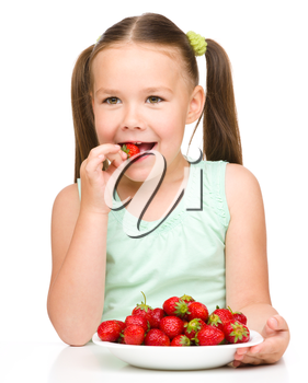 Happy little girl eats strawberries and shows the thumb up sign, isolated over white