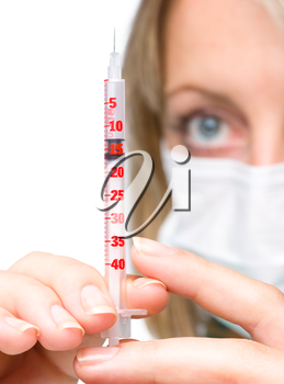 Young nurse is preparing syringe for injection while wearing surgical mask, isolated over white