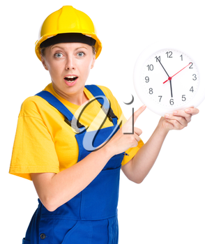 Young construction worker is pointing at clock showing almost six, isolated over white