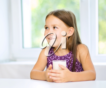 Cute cheerful little girl with a glass of milk