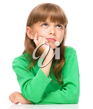 Portrait of a pensive little girl touching his cheek with index finger, isolated over white