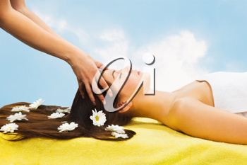 Royalty Free Photo of a Woman Getting a Scalp Massage With Daisies on Her Hair