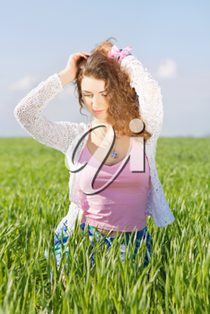 Portrait of charming young woman in a green field