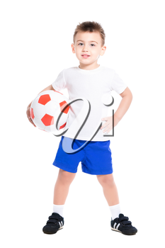 Nice little boy posing in football uniform with ball. Isolated on white