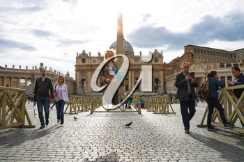 VATICAN CITY , ITALY - MAY 03, 2014: Happy girl jumping in the sunshine on the Saint Peter's Square