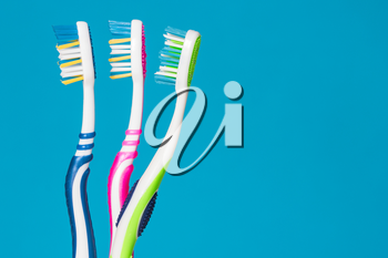 Three tooth brushes on the blue background