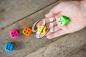 Hand throwing colorful dice  on the old wooden floor.