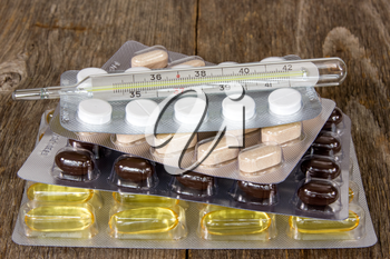 Royalty Free Clipart Image of Pills and a Thermometer