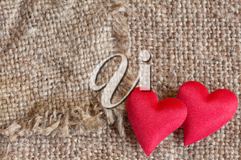 Two red decorative hearts on canvas background