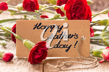 Father's day card with carnations on wooden board