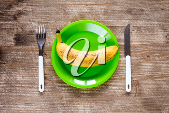 Fork,knife and green plate with banana on wooden background.