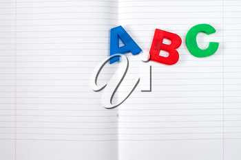 Lined exercise book and ABC letters. Back to school concept.
