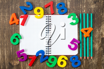 Open notebook with four pencils and colored numbers on the wood background