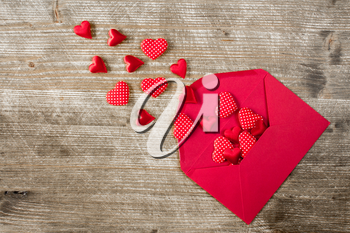 Open envelope with red hearts on the wooden background