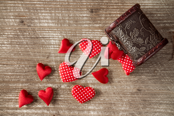 Wooden box with a pile of red hearts