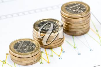 Stack of Euro coin on printed financial diagram. Shallow DOF.