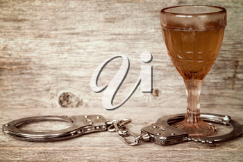 Glass of alcohol with handcuffs as symbol for alcohol abuse