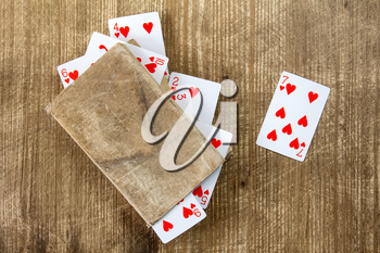 Old book and playing cards on wooden background