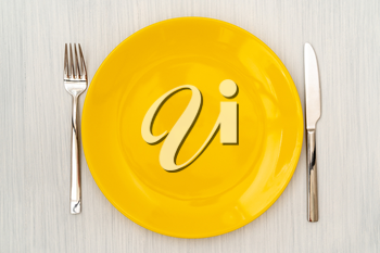 Empty yellow plate with fork and knife. View from above.