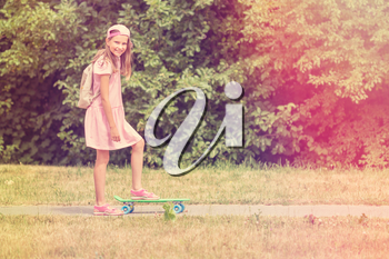 Little girl child with skateboard in a summer park
