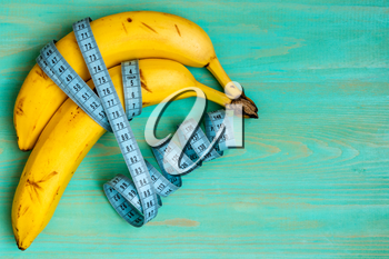 Bananas and measuring tape on wooden background.Healthy eating or dieting concept